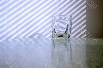 Glass of water and jalousie shadow
