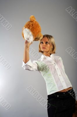 Young woman playing with the teddy bear`s head
