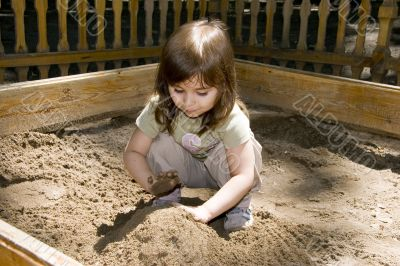 Child girl plaing at sand-box in summer park