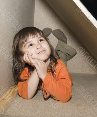 Child girl hiding in wooden box, dreams alone
