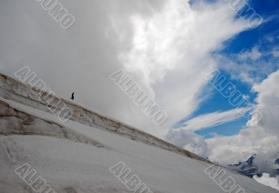 Climber making their descent down a snowy slope