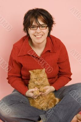 young beautiful woman holding a domestic red cat