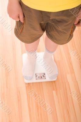 Boy measures weight on floor scales