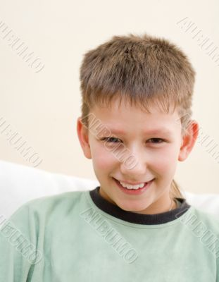 Smiling teenager sit on white sofa