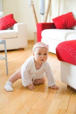 Happy baby girl crawling on a hardwood floor