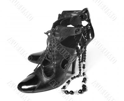 Pair of female classic shoes with necklace