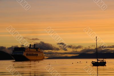 Big passenger ship and yacht at sunrise.