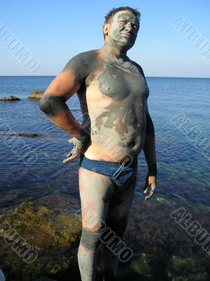 Man, smeared by therapeutic mud at sea