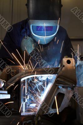 Welder welding a metal part in an industrial environment