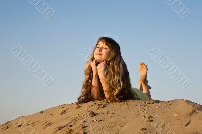 blond girl lying on the beach