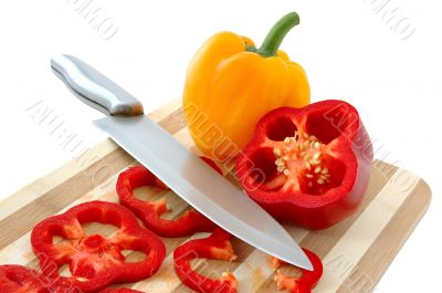 Red and yellow paprika on bamboo cutting board.
