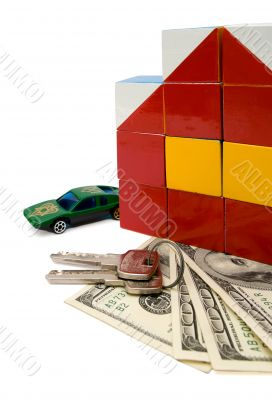 Toy house and a car over a bunch of dollars, isolated with clipp