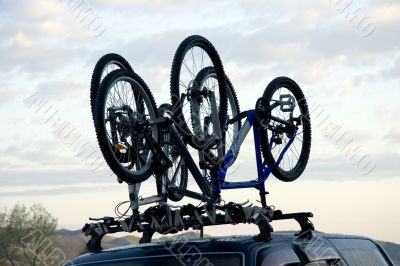 Three sports bicycles over jeep at sunrise in trip
