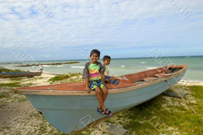 two kids relaxing on top of a fishing boat