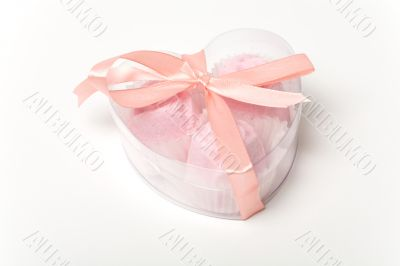 Little pink cakes in a heart shaped box over white