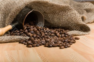 Sackcloth bag with cezve and roasted coffee beans on table