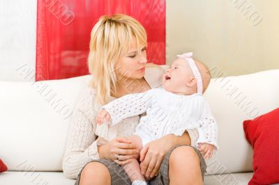 Mother hold her baby girl at home