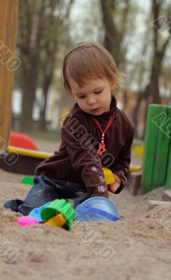 Little beauty girl playing at sand-box