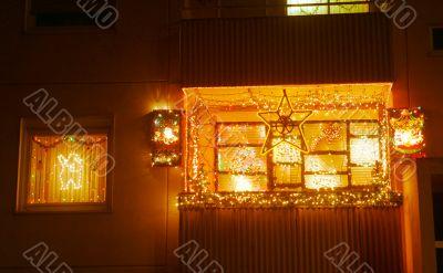 balcony and windows lighting up to Christmastime