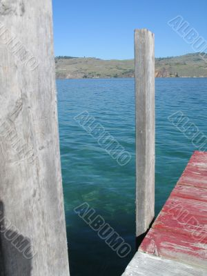 dock on the edge of a green lake