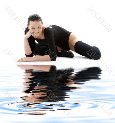 sporty girl in black leotard on white sand