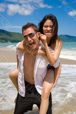 playful couple at the beach pulling ears