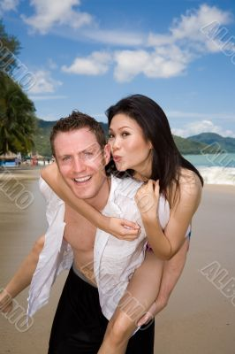 happy playful couple at the beach