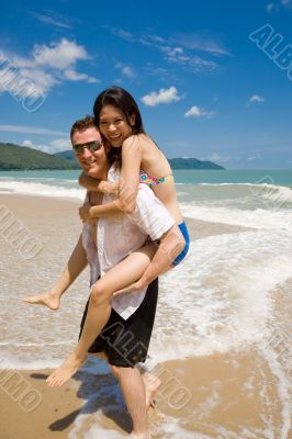 hunk carrying woman piggyback style ath beach
