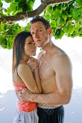 couple hugging by beach