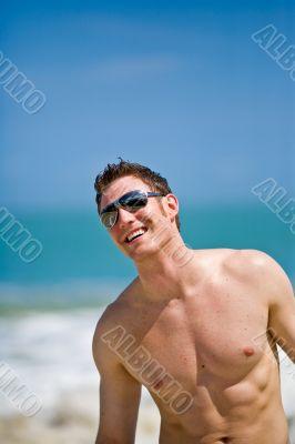 caucasian hunk at the beach with shades