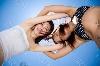 girls friend having fun under sunny blue sky