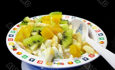 Fruit salad in a plate on a black background