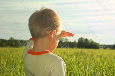 happy young boy looking horizon and dreaming on green field
