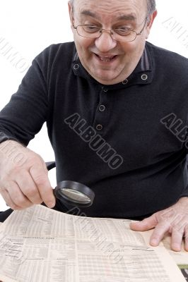 Senior read newspaper with magnifying glass