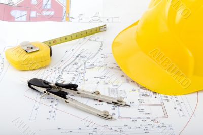 Building plan with safety helmet, pair of compasses and rolling