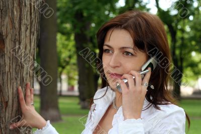 young woman is talking by mobile phone in a park