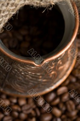 Cezve with freshly roasted coffee beans on sackcloth