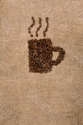 Coffee beans in the shape of a cup on sackcloth