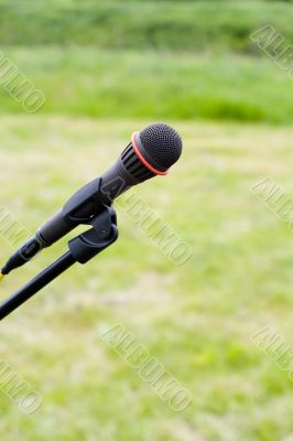 Microphone on air over green grass at background