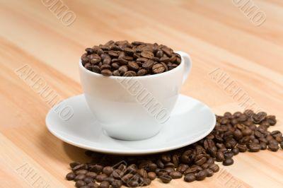 Cup with freshly roasted coffee beans on hardwood floor
