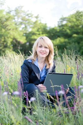 Businesswoman sitting on grass with laptop