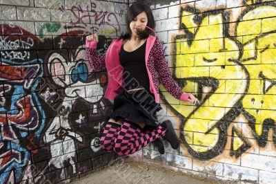 Teenager jumps before graffiti wall