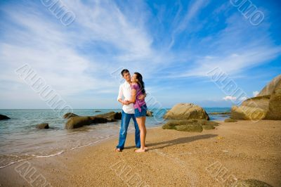 loving couple hugging each other on the summer beach