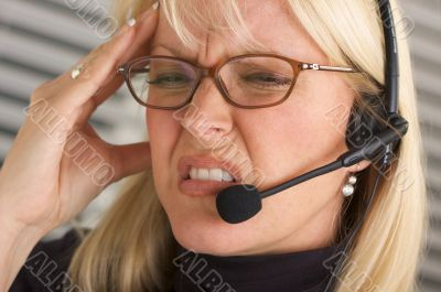 Businesswoman with Phone Headset and Headache