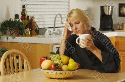 Woman Holding Head in Kitchen