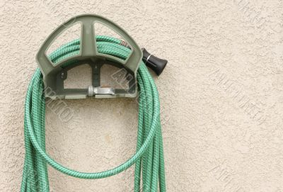 Garden Hose Hanging on Stucco Wall