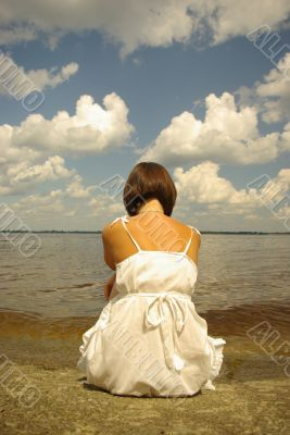 Attractive girl sitting and contemplating aloun near the river