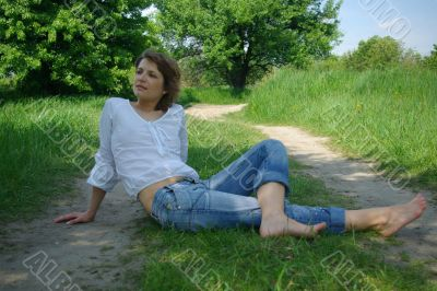 A young attractive woman sitting in a path on a warm summer day