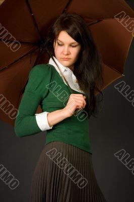 Girl in green sweater holding umbrella