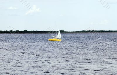 sunny sailboat in windy blue ocean
